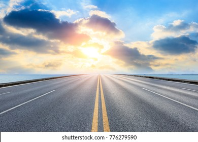 empty asphalt highway and blue sea nature landscape at sunset