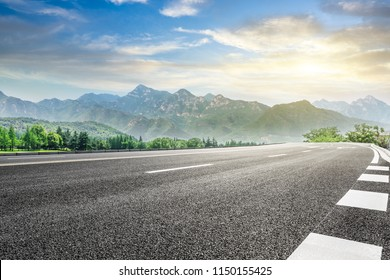 Empty asphalt highway and green mountain nature landscape at sunset