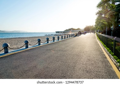 Empty asphalt highway and sea landscape at sunset.