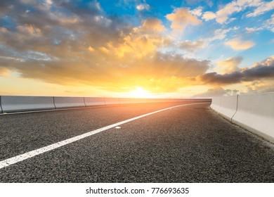 Empty asphalt highway and sky clouds landscape at sunset