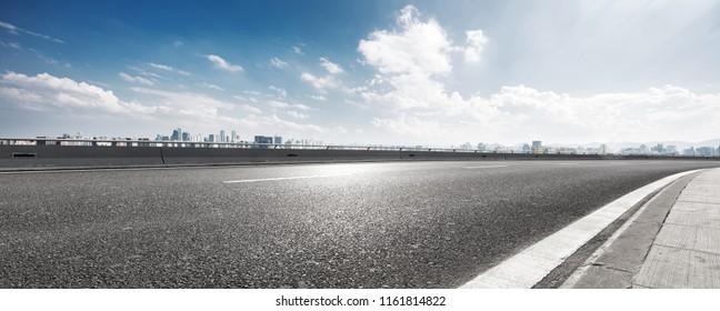 empty asphalt highway street with city skyline