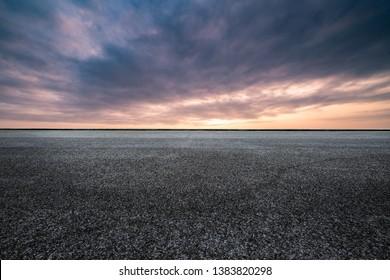 An empty asphalt highway at sunset