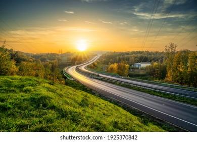 Leere asphaltierte Autobahn, die sich durch bewaldete Landschaft in Herbstfarben bei Sonnenuntergang zieht