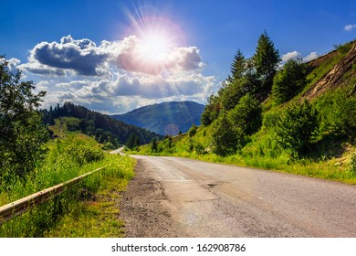 Empty asphalt mountain road with Painted single white Line near the coniferous forest with cloudy sky in morning light