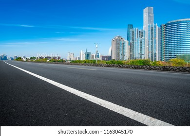 Empty asphalt road along modern commercial buildings in China's