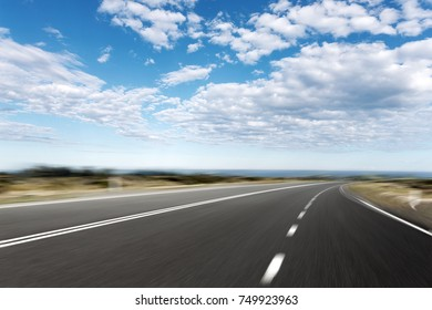 empty asphalt road and beautiful sea in blue cloud sky