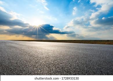 Leere asphaltierte Straße und schöne Sonnenuntergangswolken am Himmel.