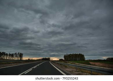 Empty asphalt road in bend on overcast spring day with light at the horizon, in Lithuania.