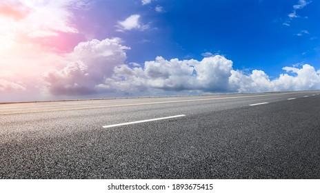 Leere Asphaltstraße und blauer Himmel mit weißen Wolken.Straßenhintergrund.
