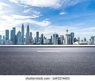 empty asphalt road with city skyline