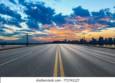 Empty asphalt road and city skyline at sunset