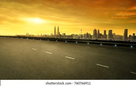 Empty asphalt road and cityscape of Kuala Lumpur city at sunset golden moment