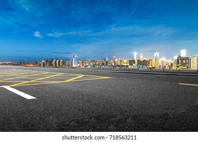 empty asphalt road and cityscape of Nanchang in blue sky at dawn