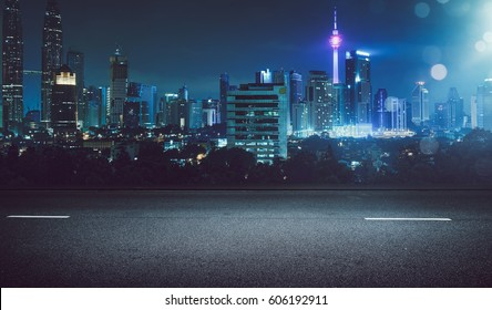 Empty asphalt road and cityscape skyline at night with light flare bokeh effect .