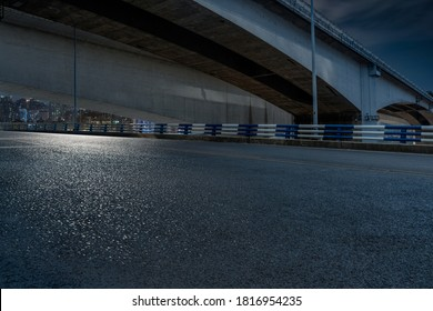 empty asphalt road in downtown under bridge at night.