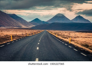 Empty asphalt road with dramatic cloudy sky. Typical icelandic landscape with volcanic hills. Image of travel concept background.