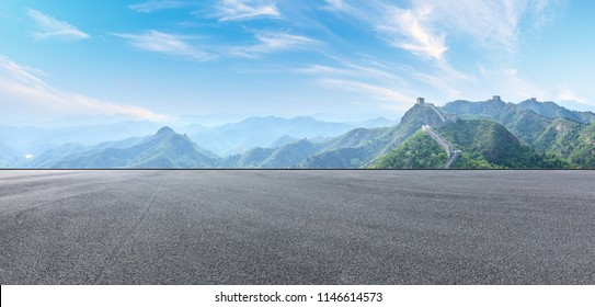 Empty asphalt road and great wall with mountains under the blue sky