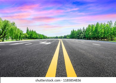Empty asphalt road and green forest with colorful clouds at sunset
