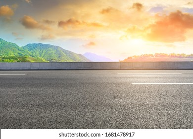 Empty asphalt road and green mountain nature landscape at sunset.
