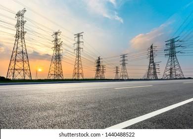 Empty asphalt road and high voltage power tower landscape