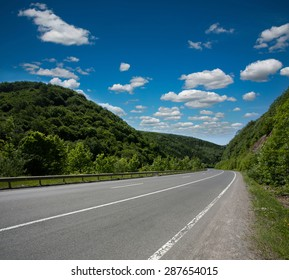 Empty asphalt road highway in the forested mountains, on the background a cloudy sky