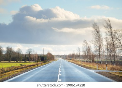 An empty asphalt road (highway) through the fields. Electricity power line close-up. Dramatic sky. France, Europe. Transportation, logistics, communications, tourism, driving, speed, freedom