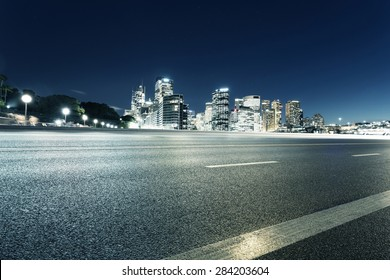 Empty asphalt road and illuminated modern cityscape background at night