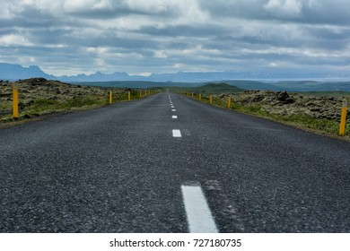 Empty asphalt road into wild nature of Iceland with green moss on sides and dramatic sky