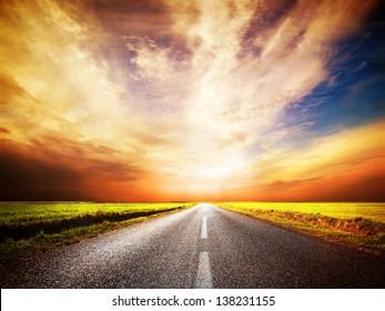 Empty asphalt road. Long and straight. Sunset Sky