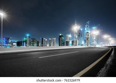 empty asphalt road and modern buildings in midtown of dubai in cloud sky at night