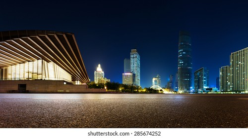 Empty asphalt road and modern skyline at night