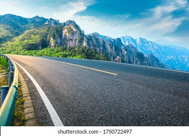 Empty asphalt road and mountain natural scenery on a sunny day.
