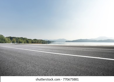 empty asphalt road near beautiful lake in blue sunny sky