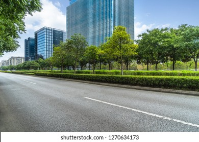 empty asphalt road near glass office building