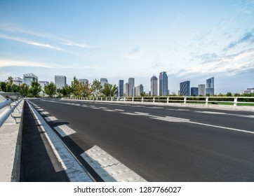 empty asphalt road on modern bridge with city skyline background