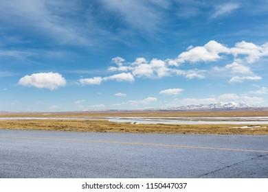 empty asphalt road on snow covered plateau against a blue sky