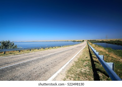 Empty asphalt road on thin neck through lake in sunny summer day. Wide angle view.
