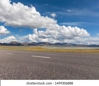 empty asphalt road and plateau lake against a blue sky, qinghai province, China