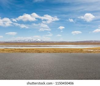 empty asphalt road and snow area plateau against a blue sky