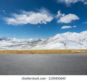 empty asphalt road and snow mountain against a blue sky