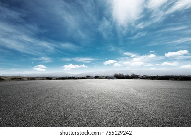 empty asphalt road and snow mountains in blue cloud sky