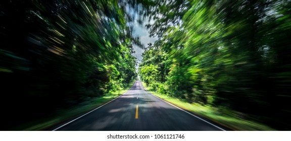 Empty asphalt road and speed motion blur on highway in summer with green trees forest at countryside