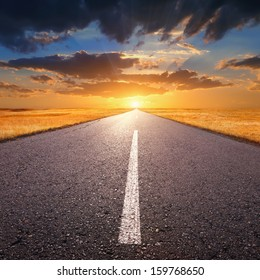 Empty asphalt road at sunset