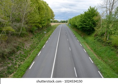 Empty asphalt road is surrounded with green roadside trees and bushes.