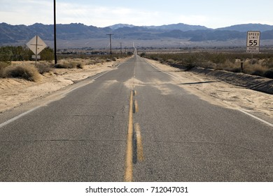 Empty asphalt road through a desert in California, USA