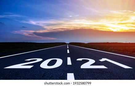 Empty asphalt road through the field and in the distance sunset. The concept for the new year 2021.