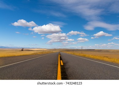 Empty Asphalt Road Through Golden Plains Under Blue Sky With Puffy Clouds