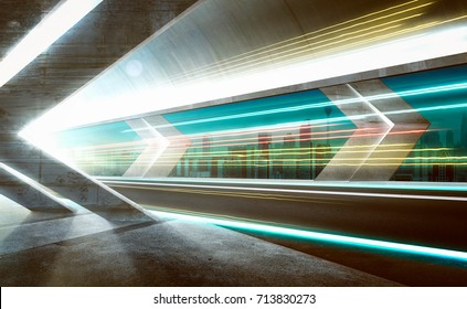 Empty asphalt road tunnel during the night with light trails and beautiful city skyline background .