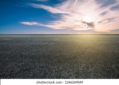 The empty asphalt road under the blue sky and white clouds