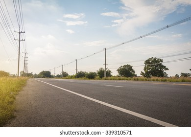 Empty asphalt road under cloudy sky